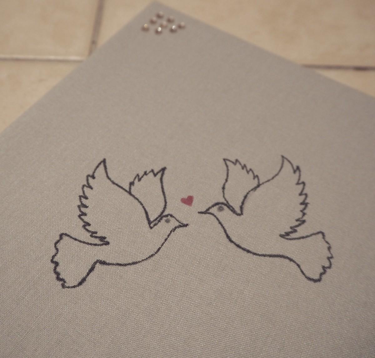 Verliebte Tauben auf dem Cover des Hochzeitsbuchs.